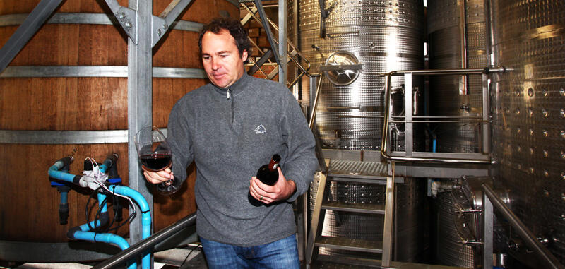 Jean-Claude checking new blends in the cellar and fetching a library stock bottle to benchmark against.
