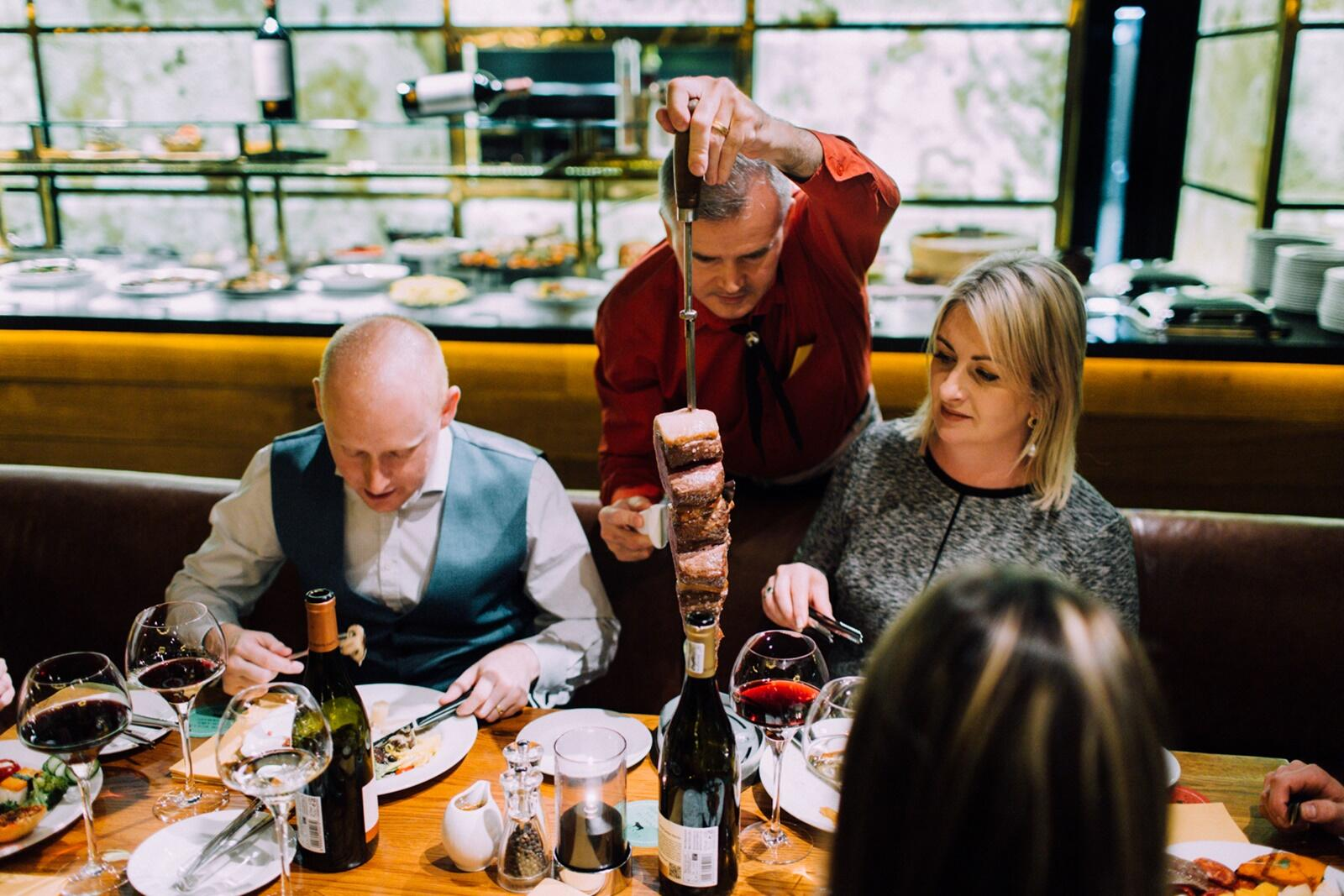 Carolyn Martin being served at Fazenda Rodizio Bar & Grill from a table-side rotisserie