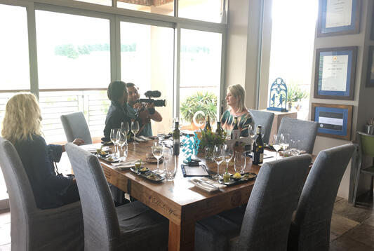 Carolyn being interviewed and filmed at a sunbathed table